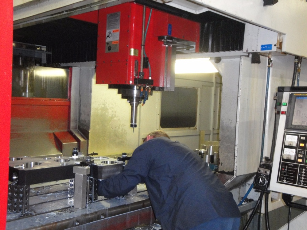 CNC Machinist Adjusting Toyoda Vertical Milling Machining Center